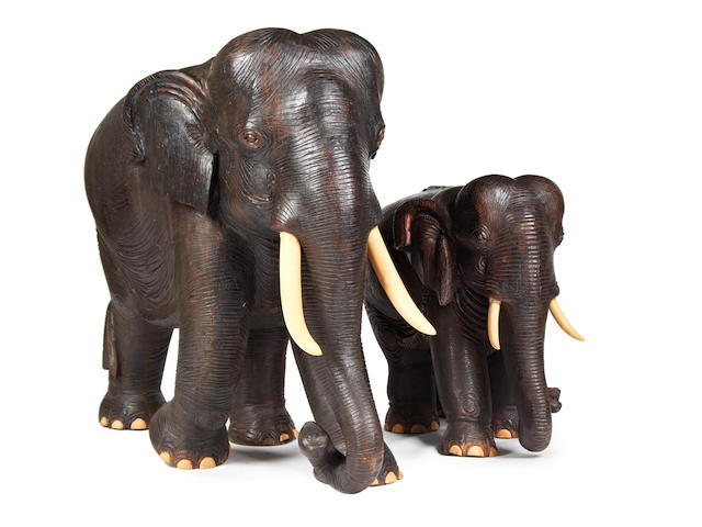 A carved hardwood model of an Indian elephant and another of a baby elephant