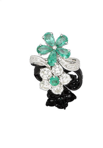 An emerald and diamond flower ring