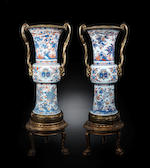 A pair of important and massive ormolu-mounted Chinese Imari armorial beaker vases, gu Circa 1715-1720, the European ormolu mounts probably first half 19th century