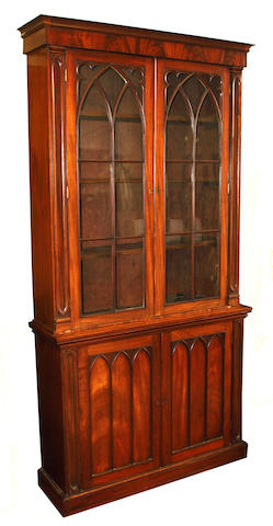 A Victorian mahogany glazed bookcase on cupboard in the Gothic manner