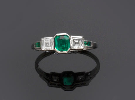 An emerald and diamond half hoop ring