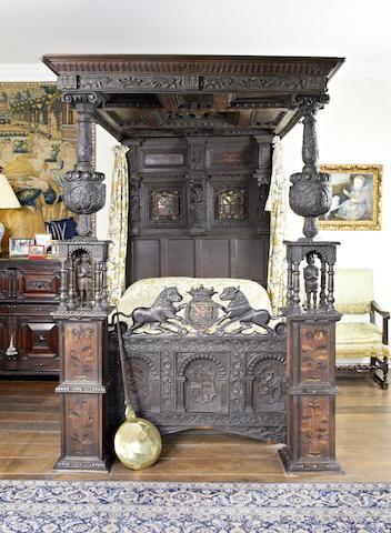 An impressive Elizabeth I oak and inlaid tester bed, circa 1580, bearing the coat of arms of the Ratcliffes of Ordsall Hall, Lancashire, incorporating some associated and some later elements