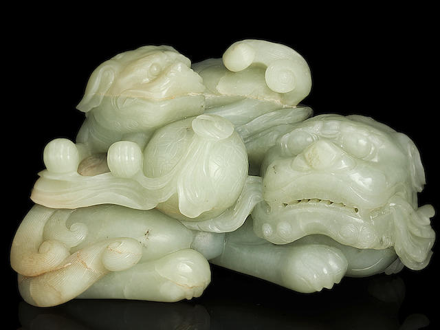 A superb large pale green jade group of a Buddhist lion and cub 18th century
