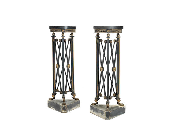 A pair of Regency ebonised and parcel gilt triform torchere stands in the manner of Thomas Hope