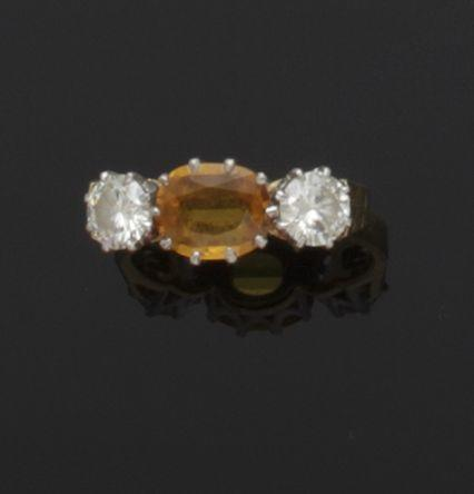 A yellow sapphire and diamond three stone ring