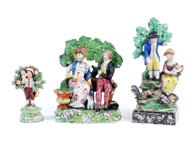Two Staffordshire pearlware figure groups and a figure of a piper 'Showman', circa 1810-20
