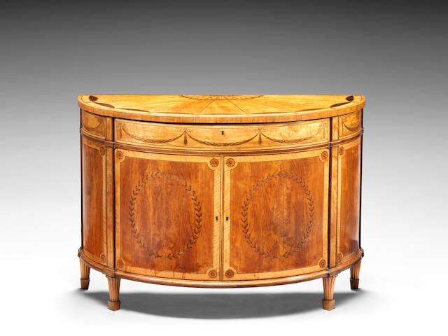 A George III satinwood, amaranth, tulipwood and marquetry demi-lune commode attributed to Thomas Chippendale