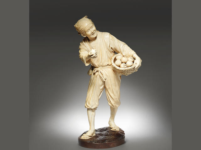 A fine and exceptionally tall ivory okimono figure of a fruit seller Meiji Period