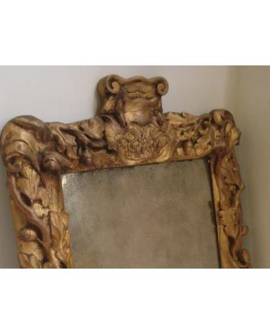 A William & Mary giltwood frame upright wall mirror, carved with trailing branches of oak leaves and acorns and scrollwork, surmounted by a cartouche with entwined monogram 'WM' late cresting and elements lacking, 64 x 48cm.