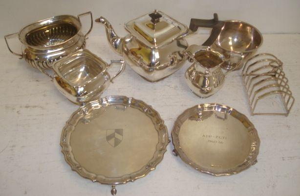An Art Nouveau three piece silver tea service by T Wilkinson, Birmingham 1904, Of bulbous angular square form, comprising teapot, sugar basin and milk jug, height of teapot 16cm, two shaped circular silver waiters, both inscribed, with remaining silver wares, weight combined 58oz.