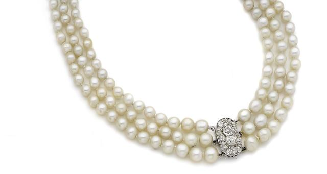 A triple-strand pearl necklace with diamond-set clasp