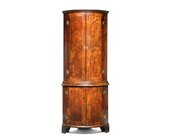 A George I walnut crossbanded and featherbanded bowfront corner cupboard