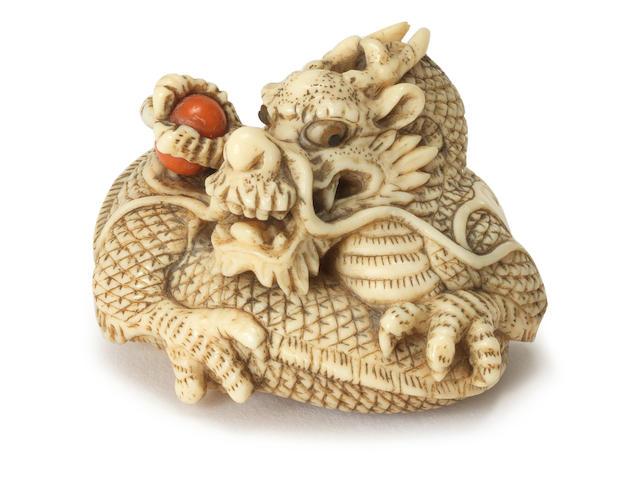 An ivory netsuke of a dragon By Yoshitomo, Kyoto, early 19th century