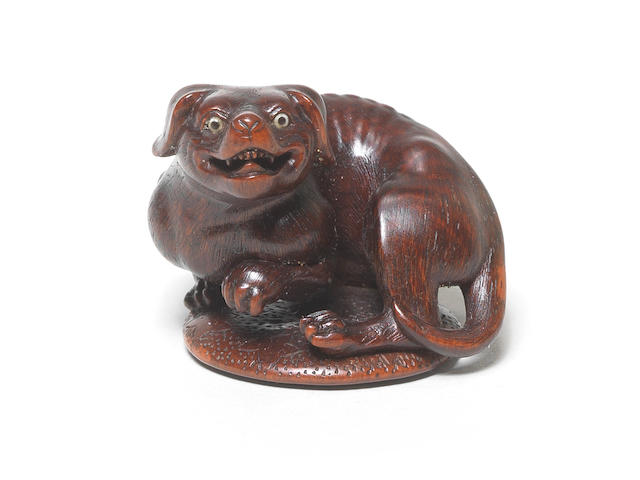 A wood netsuke of a dog By Hoshin, Kyoto, late 18th/early 19th century