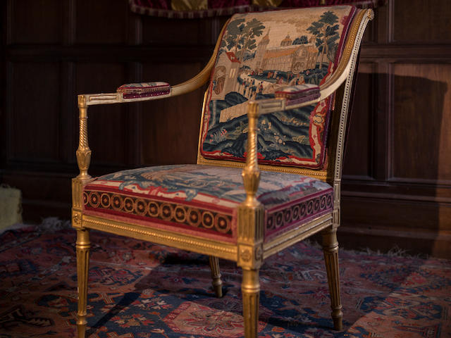 An important set of seven George III giltwood framed open armchairs