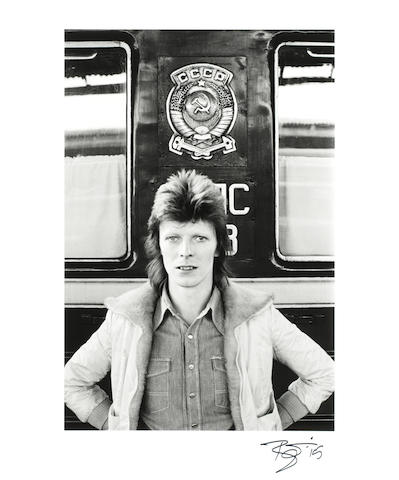 Geoff MacCormack (English b. 1947): a black and white silver gelatin print of David Bowie in front of the Trans-Siberian Express, signed by David Bowie,