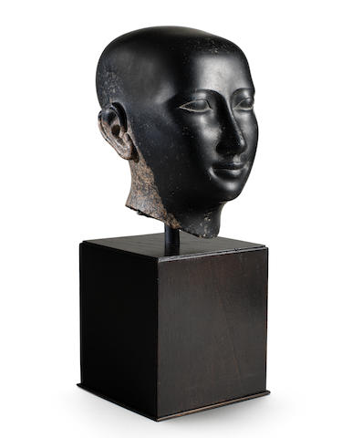 An Egyptian granite head of a priest