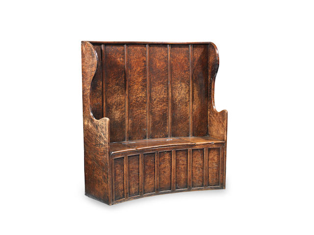An impressive George III boarded and joined pollard-oak curved box-settle, West Country, circa 1800