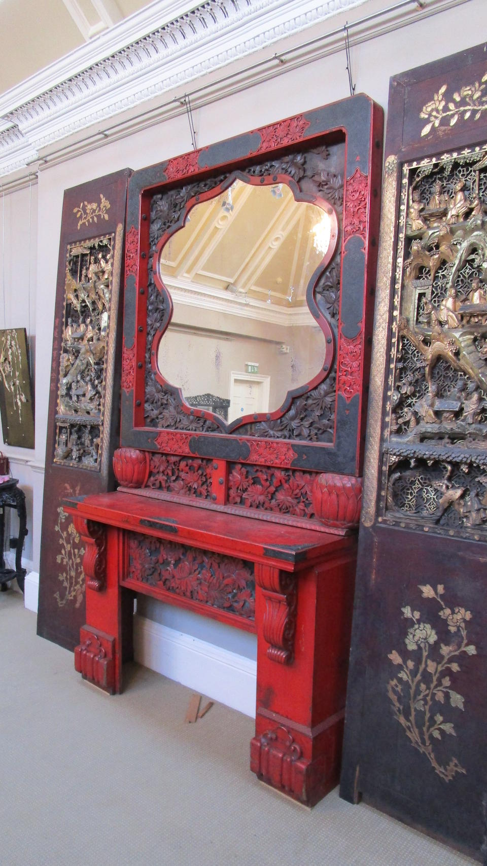 An Anglo-Japanese Carved and Red-Lacquered Chimney-piece and Mirrored Overmantel POSSIBLY BY THOMAS JECKYLL (ENGLISH, 1827-1881); CIRCA 1870s