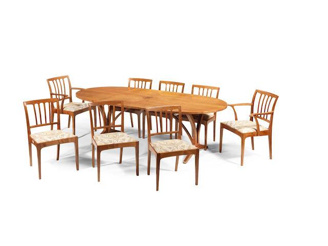 Edward Barnsley (British, 1900-1987): A dining table and eight chairs, Executed 1977/1978 English walnut with sycamore cross-banding,  73cm high, 228cm wide (28 3/4in high, 89 3/4in wide)