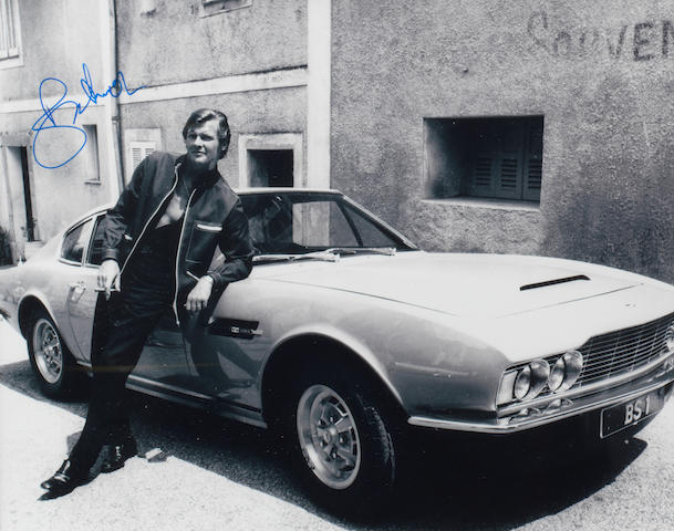 A signed photograph of Roger Moore with the 'Persuaders' Aston Martin DBS,