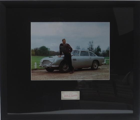 A photograph with signature of Sean Connery with the James Bond 'Goldfinger' Aston Martin DB5,
