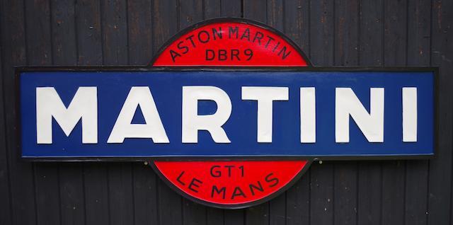 An 'Aston Martin Martini DBR9' sponsorship sign,