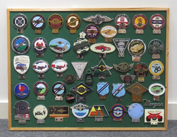 A framed display of Morgan Car Club badges,