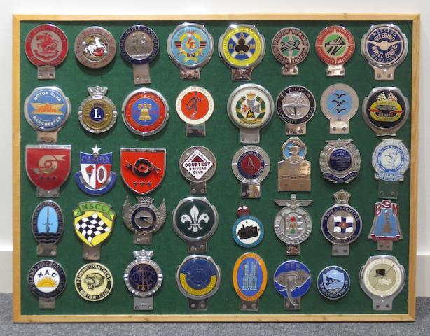 A framed display of British car badges,