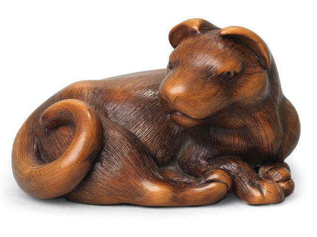 A wood netsuke of a recumbent dog  By Masanao, Kyoto, late 18th century