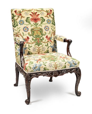 A George III carved mahogany and parcel gilt Gainsborough chair, circa 1760, in the manner of Saunders and Bradshaw