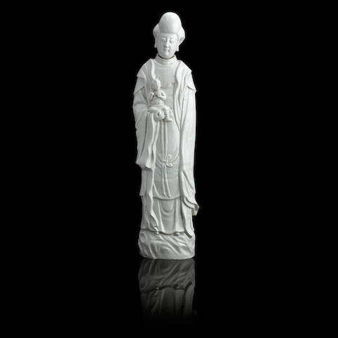 A tall blanc-de-chine figure of Guanyin and boy Late 17th/early 18th century