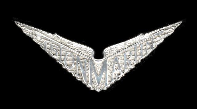 A CAST ALUMINIUM SIGN DEPICTING THE PRE-WAR ASTON MARTIN WINGED EMBLEM,