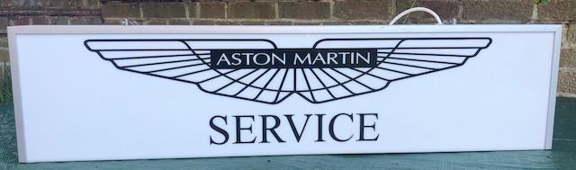"An ""Aston Martin Service"" illuminated hanging sign,"