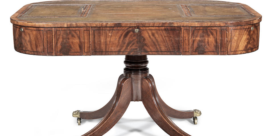 An unusual Regency mahogany and ebonised line-inlaid drum top partners' library table