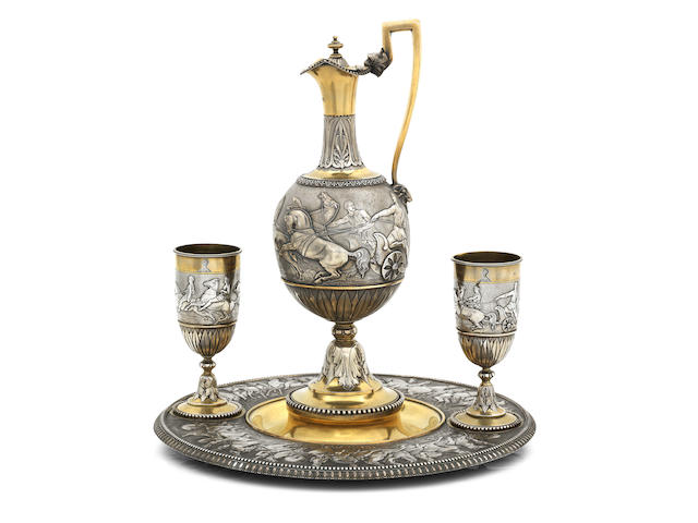 A Victorian parcel-gilt vase shaped wine ewer and pair of goblets on stand by Stephen Smith, London 1866, signed Stephen Smith, 35 King Street, Covent Garden, London