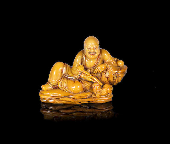 A gilt-decorated soapstone carving of the Laughing Lion Luohan 20th century (2)
