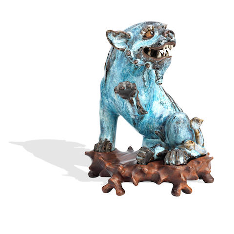 A Shiwan lion dog on wood stand Late 19th century
