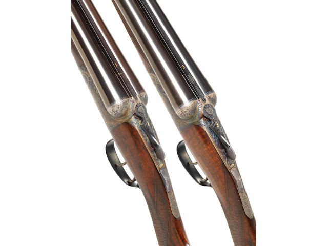 A fine pair of Lee-engraved 12-bore round-action ejector guns by David McKay Brown, no. 7475/6 In their brass-mounted oak and leather case with canvas cover