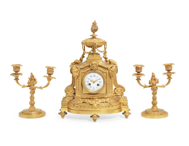 A late 19th century French clock together with a pair of matched garniture candelbra both in the Louis XVI style