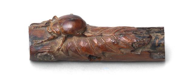 An umimatsu (sea-pine) netsuke of a beetle on a decaying branch By Tsuramitsu (Kanman, 1793-1859), Iwami Province, first half of the 19th century