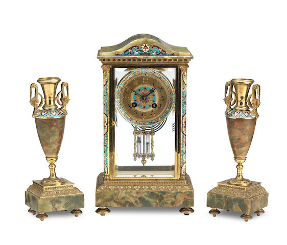 A late 19th/early 20th century French champleve enamel and onyx clock garniture