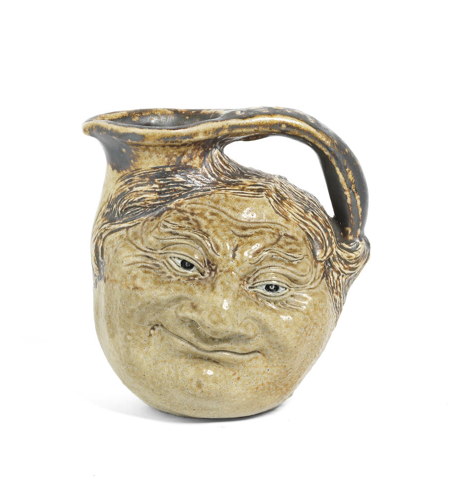 The Martin Brothers (British, active 1873-1903) A Double-Sided Stoneware Pottery Face Jug, circa 1935