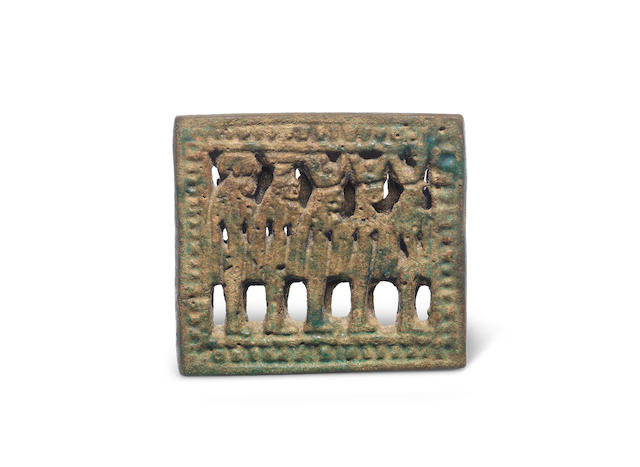 An Egyptian turquoise glazed composition plaque with five goddesses