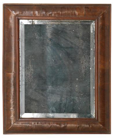 An early 18th century walnut cushion framed wall mirror