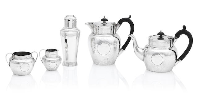 A matched four piece hammered silver bachelor's tea service the teapot by Charles Bradbury & Sons, Ltd, Sheffield 1907, hot water pot by J&T, Sheffield 1927, cream jug and sugar bowl by Saunders and Shepherd, Birmingham 1903