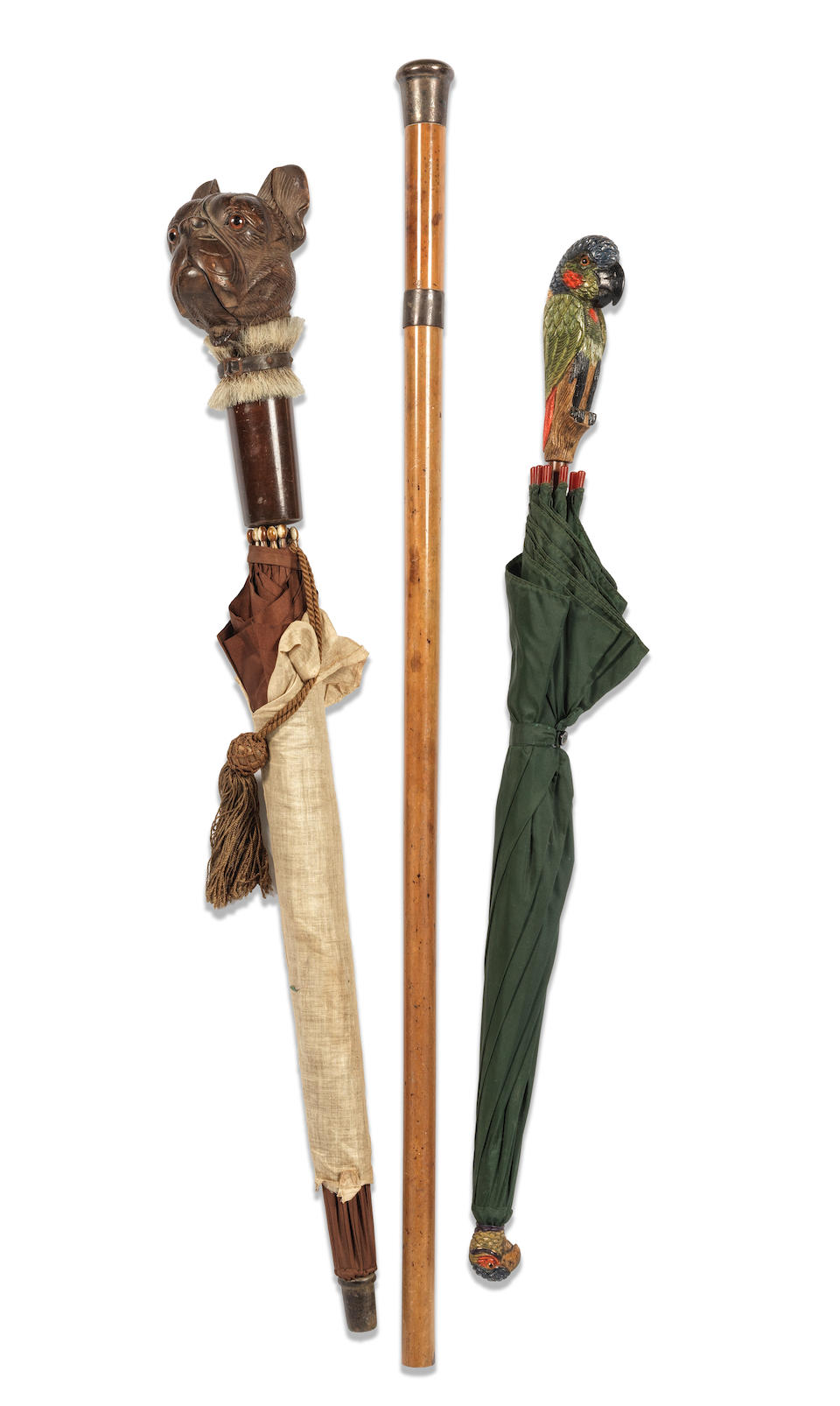 An early 20th century Black Forest carved and stained wood French bull dog's head handled novelty umbrella together with a carved and polychrome stained parrot's head novelty umbrella and a silver mounted malacca walking cane (3)