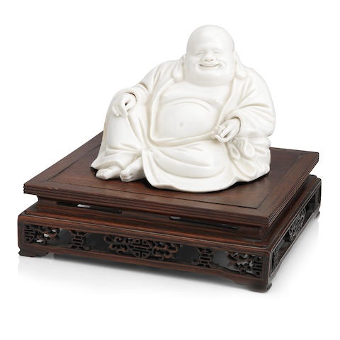 A well-modelled blanc-de-chine figure of Budai on wood stand Early Qing Dynasty