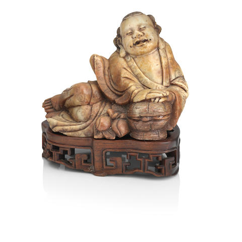 A large soapstone figure of Daoist Immortal on wood stand Qing Dynasty, 19th century