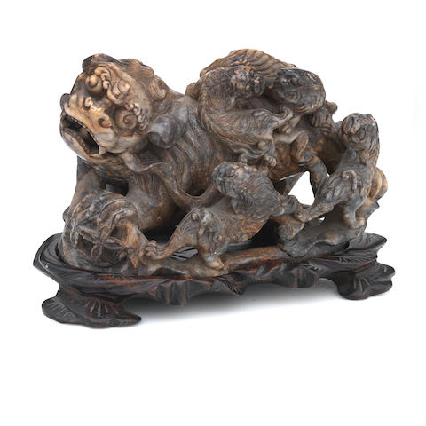 A soapstone model of a Buddhist lion dog and cubs on stand 19th century